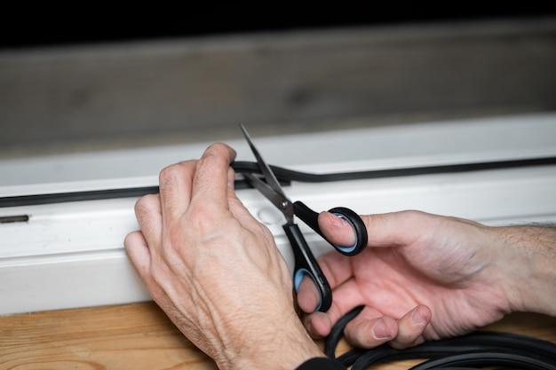 Technicien professionnel de réparation et d'installation de fenêtres, coupe le caoutchouc d'étanchéité pour l'installation dans une fenêtre en pvc
