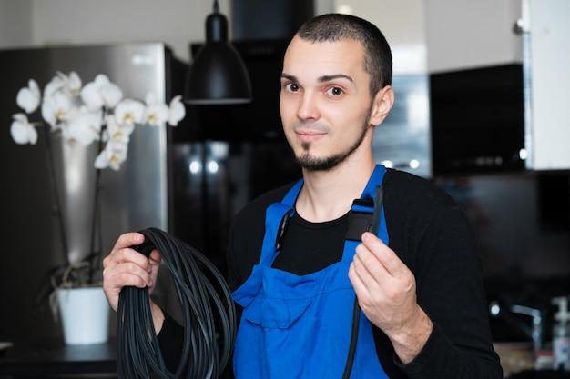 Technicien professionnel de réparation et d'installation de fenêtres tenant un joint en caoutchouc pour les fenêtres en pvc dans sa main.