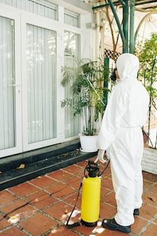 Technicien de pulvérisation de produits chimiques sur la maison