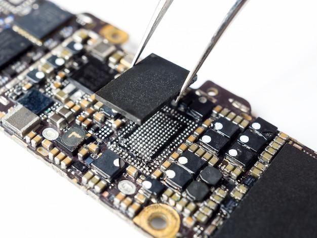 Technicien remplaçant le ci d'alimentation de la carte mère de smartphone