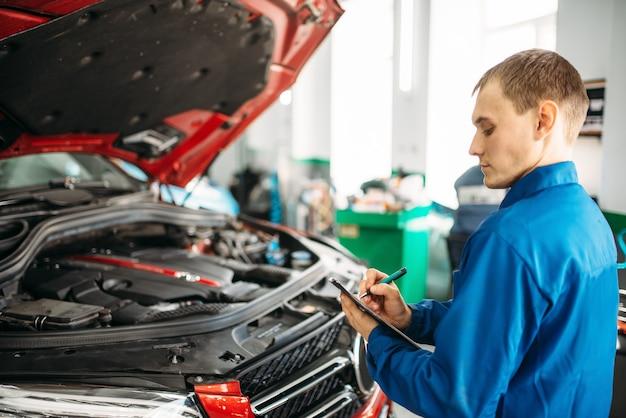 Le technicien remplit la liste de contrôle, voiture avec capot ouvert