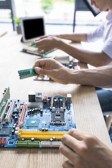 Technicien réparant la carte mère de l'ordinateur