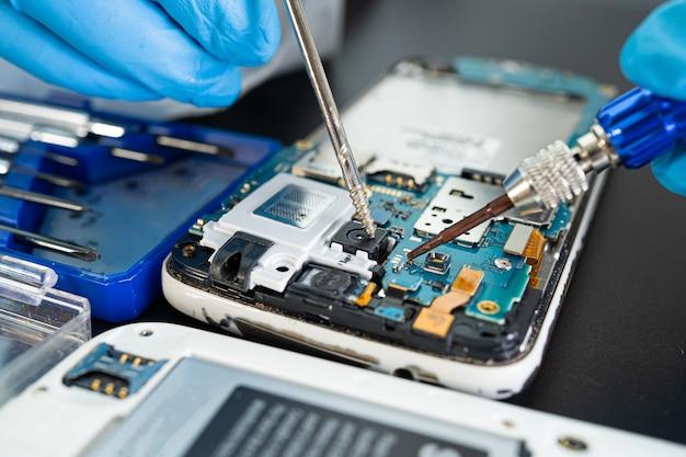 Technicien réparant à l'intérieur du téléphone mobile par fer à souder