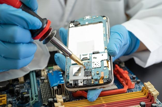 Technicien réparant l'intérieur du téléphone portable par fer à souder. circuit intégré. le concept de données, de matériel, de technologie.