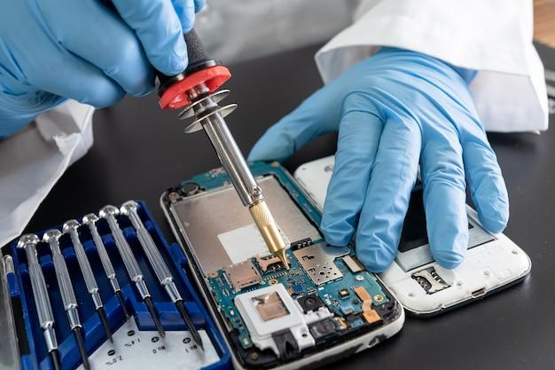 Technicien réparant à l'intérieur du téléphone portable par le fer à souder