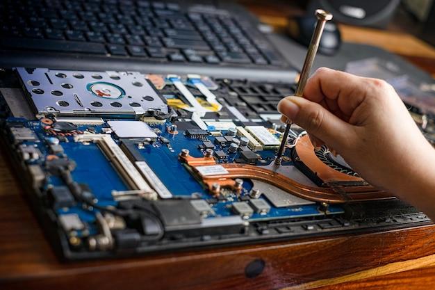 Technicien réparant un ordinateur portable cassé avec un tournevis