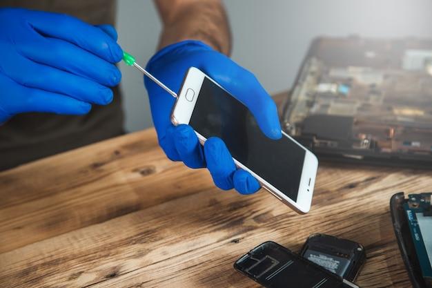 Technicien réparant un téléphone mobile à table