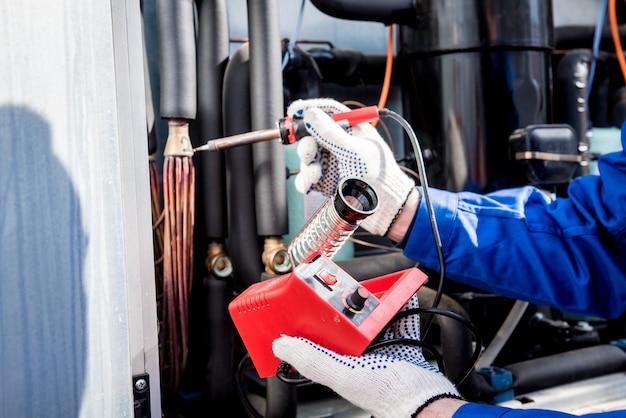 Le technicien répare les capteurs de température électroniques avec un fer à souder électronique