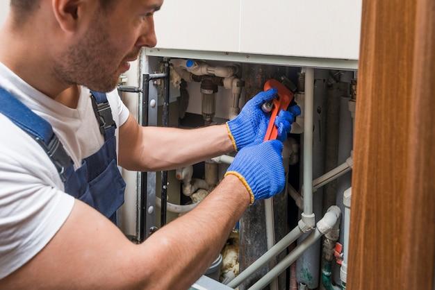 Technicien sanitaire travaillant avec des tuyaux