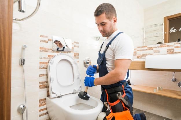 Technicien Sanitaire Utilisant La Tasse De Force Photo Premium