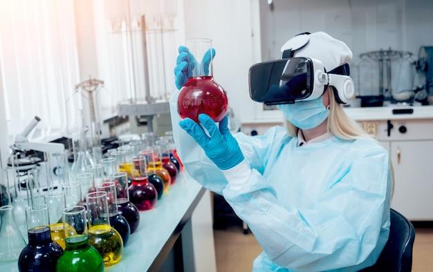 Un technicien scientifique en lunettes de réalité virtuelle examine le médicament en laboratoire.