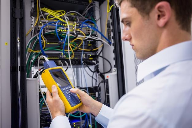 Technicien sérieux utilisant un analyseur de câble numérique sur serveur