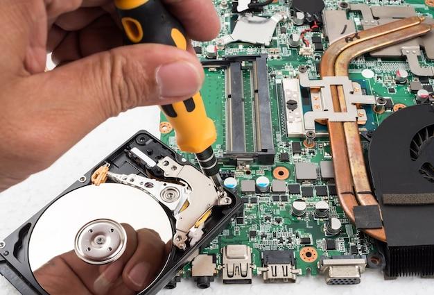 Technicien supporte la partie mise à niveau et la fixation de l'ordinateur portable.