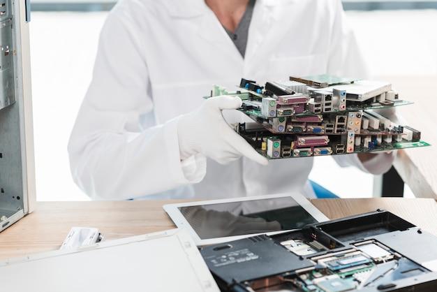 Technicien tenant des pièces d'ordinateur en atelier