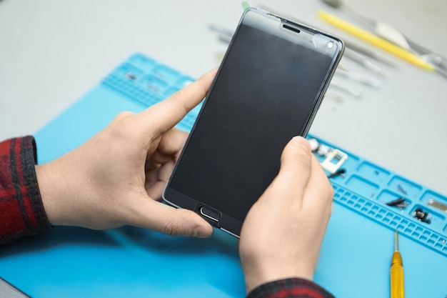 Technicien tenant un téléphone intelligent, va éliminer les bulles d'air dans le verre trempé fixé sur le gadget