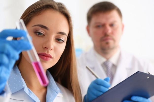 Technicien tenir dans les bras dans la bouteille d'échantillon de gants de protection