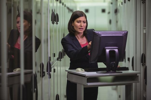 Technicien travaillant sur ordinateur personnel lors de l'analyse du serveur