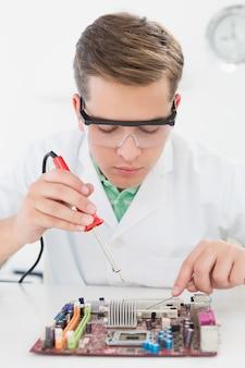 Technicien travaillant sur une unité de traitement cassée avec un fer à souder