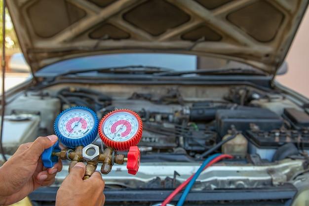Technicien utilisant un équipement de mesure pour le remplissage des climatiseurs de voiture. concepts de service de réparation automobile et d'assurance automobile.