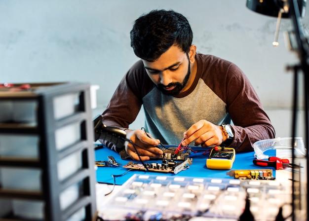 Technicien utilisant un multimètre avec des composants électroniques