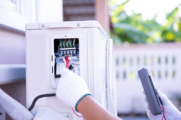 Technicien utilisant un outil de mesure vérifiant l'électricité au compresseur d'air extérieur.