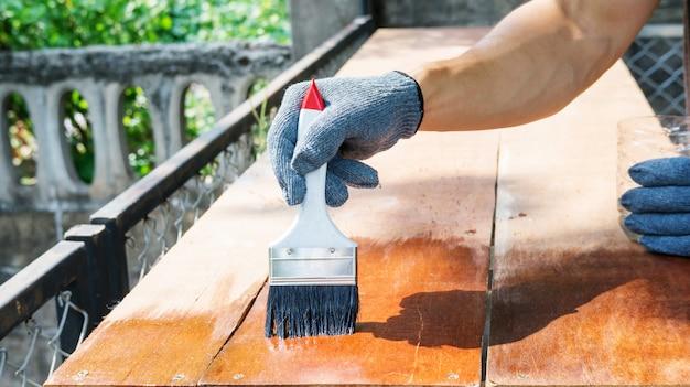 Technicien en utilisant une peinture vernis avec une table en bois.