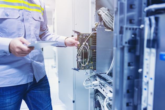 Technicien utilisant une tablette numérique dans la salle des serveurs, carte mère de la carte de réparation vérifiant l'état de la liaison réseau