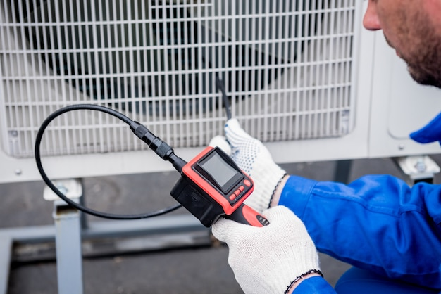 Le technicien utilise un appareil photo numérique pour vérifier le colmatage de l'échangeur de chaleur