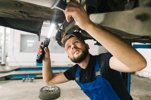 Technicien vérifiant le fond du véhicule