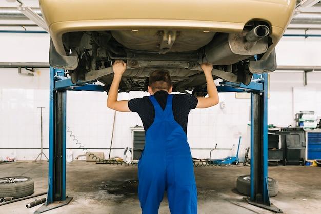 Technicien vérifiant la transmission de la voiture