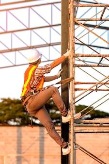 Un technicien en vêtements de sécurité monte des échafaudages