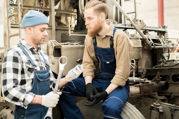 Techniciens automobiles discutant du travail
