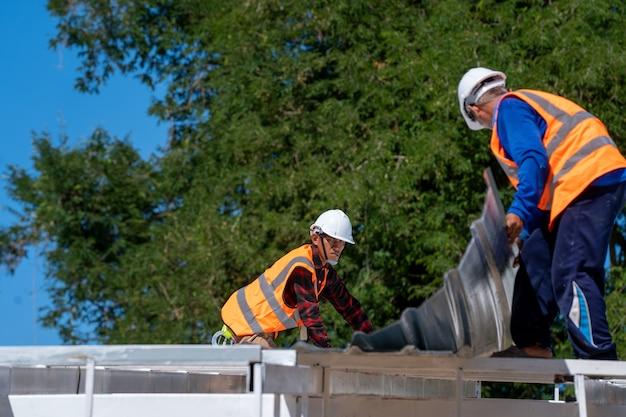 Les techniciens couvreurs travaillent et installent une nouvelle structure de toit sur le toit supérieur de la maison, le toit en métal, les attaches en tôle ondulée.
