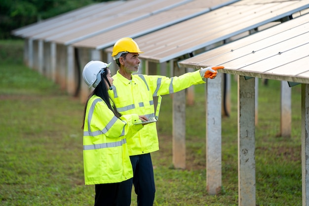 Techniciens et ingénieur en chemises à manches longues, gilets réfléchissants et casques de sécurité discutant de la puissance des panneaux solaires.