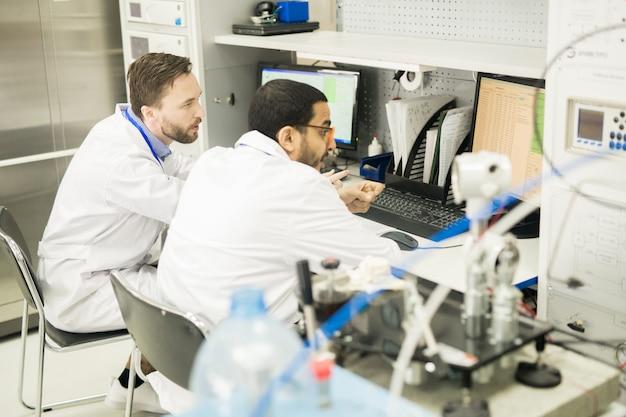 Techniciens occupés à visualiser les données dans le bureau d'usine