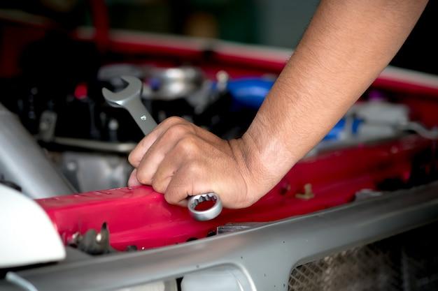 Les techniciens en réparation de moteur tiennent la clé en main pour réparer la voiture.
