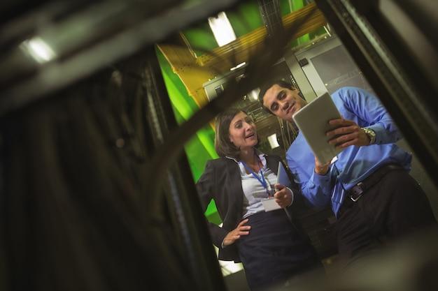 Techniciens utilisant une tablette numérique lors de l'analyse du serveur