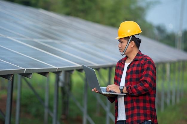 Les techniciens vérifiant les panneaux solaires, la production d'énergie verte écologique bon marché renouvelable concep