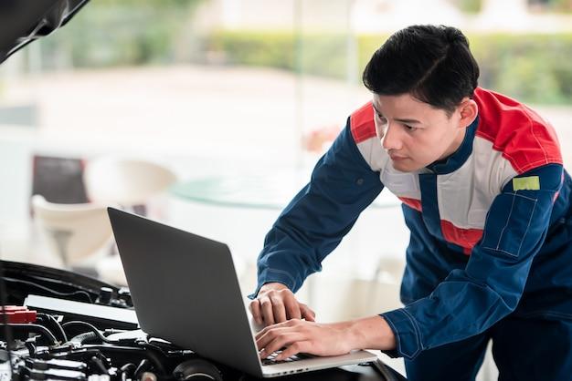 Les techniciens vérifient et réparent les voitures dans le garage les techniciens de l'atelier de réparation automobile utilisent des systèmes informatiques pour vérifier les problèmes de moteur - services de réparation automobile, concepts de maintenance.