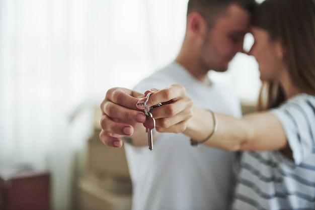Technique de mise au point d'image. les clés de la maison. joyeux jeune couple dans leur nouvel appartement. conception du déménagement.