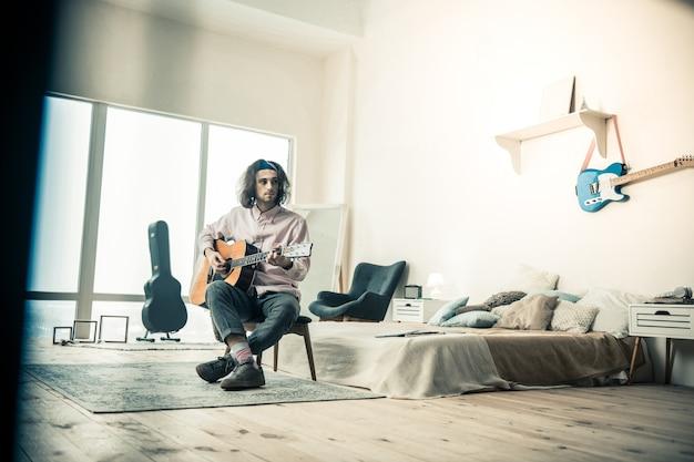 Techniques et sons. artiste masculin solitaire et beau passant sa journée avec un bel instrument assis sur une chaise dans la chambre