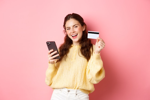Technologie et achats en ligne. cliente heureuse et satisfaite, montrant une carte de crédit en plastique et utilisant une application de téléphonie mobile pour payer en ligne, debout contre un mur rose.