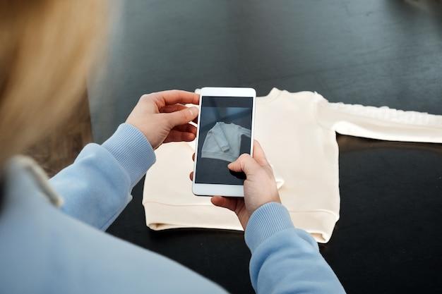 La technologie ar vr dans l'industrie de la mode, une créatrice de vêtements qui tire des vêtements sur un mannequin par téléphone portable pour