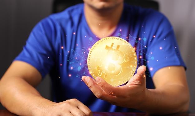 Technologie blockchain et concept de réseau homme tenant la main de bitcoin avec une connexion réseau d'icônes