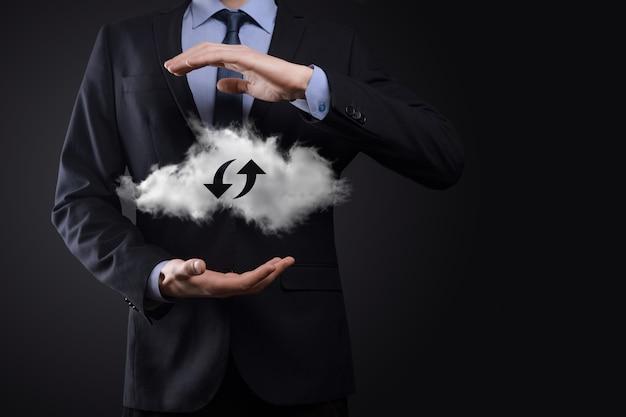 Technologie cloud. signe de stockage en nuage avec deux flèches de haut en bas sur l'obscurité