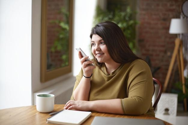 Technologie, communication et style de vie modernes. adorable belle jeune femme brune avec un corps sinueux enregistrement message vocal via l'application de messagerie en ligne à l'aide de téléphone mobile à table de café