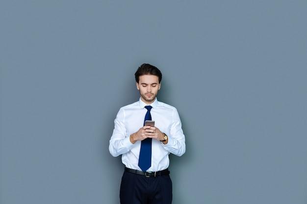Technologie digitale. smart nice bel homme d'affaires debout et à l'aide de son smartphone tout en tapant un message