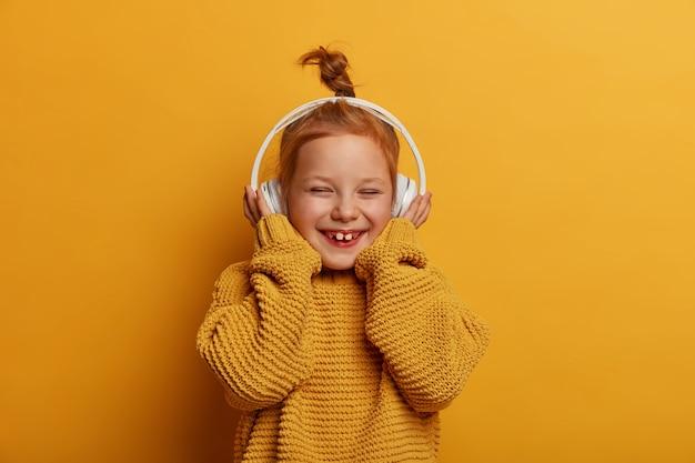 Technologie, enfants, concept de musique. petit enfant assez souriant aux cheveux roux porte des écouteurs stéréo, apprécie le son pur et écoute la chanson préférée, rit joyeusement, porte un pull en tricot