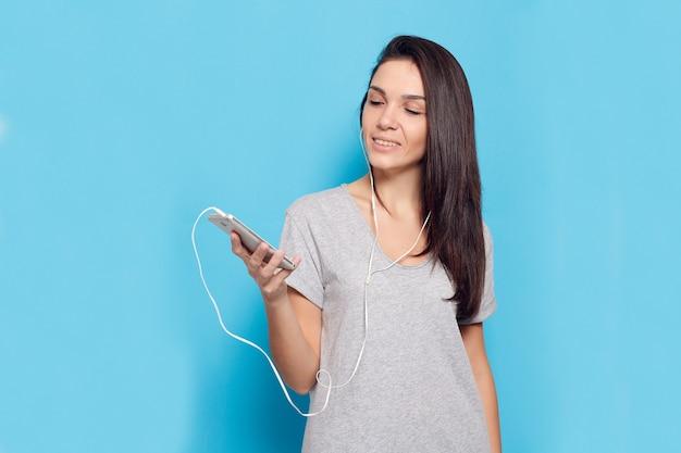 Technologie, mode de vie, dépendance à internet et concept de personnes - belle jeune femme avec un téléphone intelligent. femme joyeuse avec un casque sur fond bleu. femme séduisante heureuse et souriante