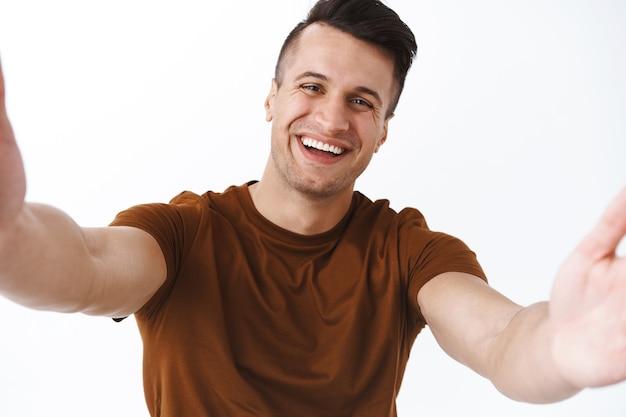 Technologie, mode de vie en ligne et concept de quarantaine. un homme adulte joyeux et joyeux discute en vidéo avec des amis pendant la pandémie de covid19, restez à la maison et restez en contact avec le monde en utilisant internet, en prenant un selfie
